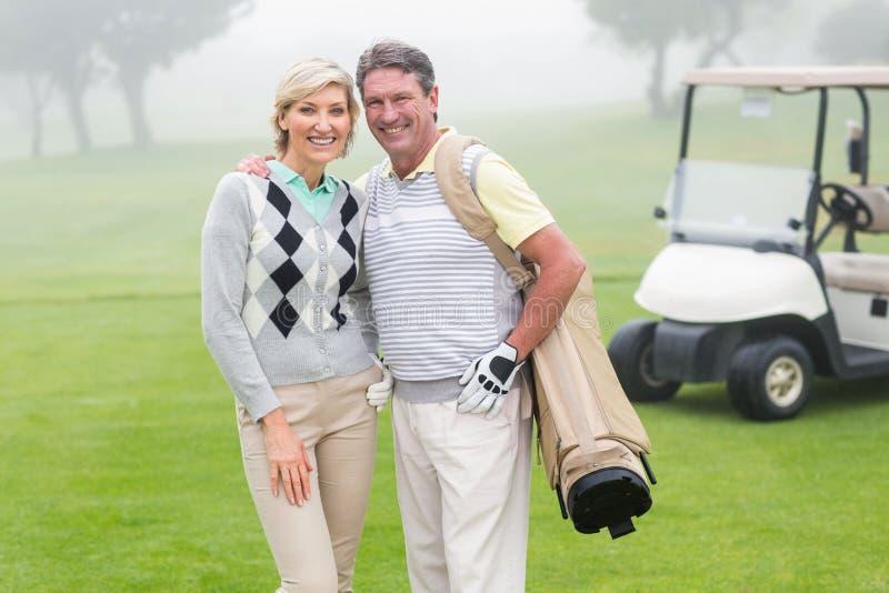 Lyckliga golfspelpar med golfbarnvagnen bakom royaltyfri bild