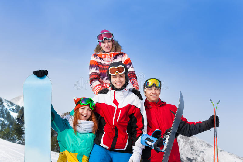 Lyckliga grabbar som står med snowboards och, skidar royaltyfria foton