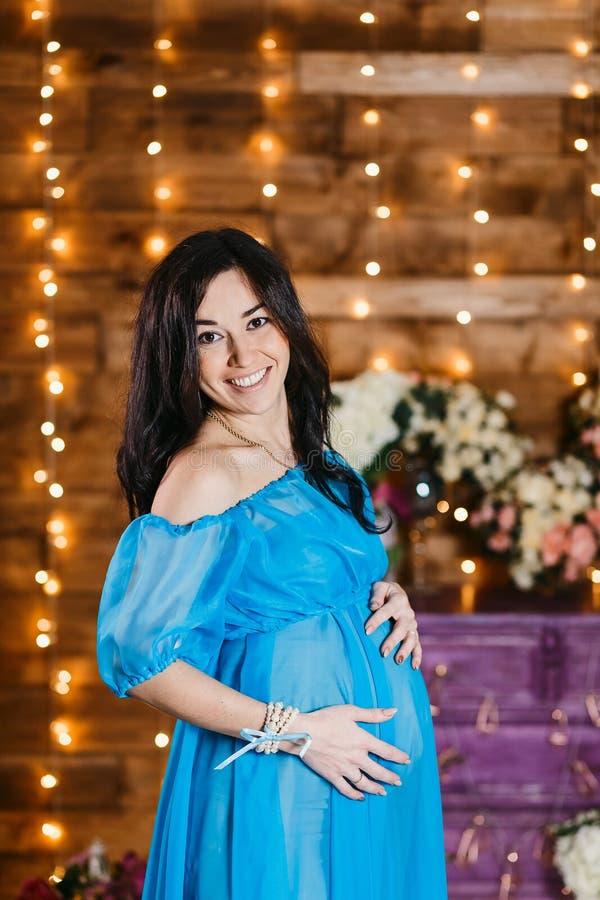 Lyckliga gravida händer för brunettkvinnainnehav på henne mage och le royaltyfri foto