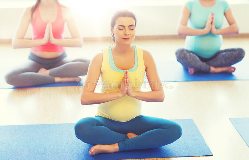 Lyckliga gravida kvinnor som övar yoga i idrottshall arkivbilder
