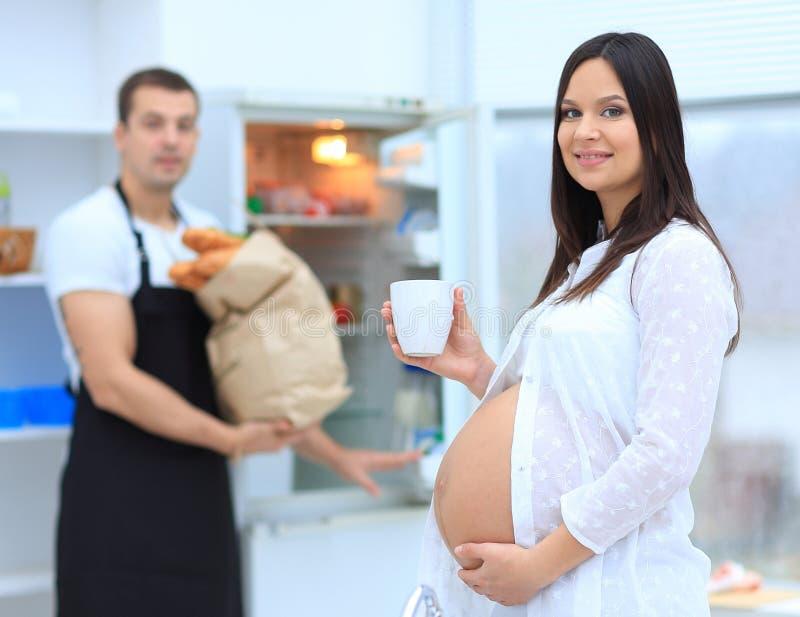 Lyckliga gravida par av vegetarian i köket fotografering för bildbyråer