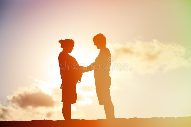 Lyckliga gravida par på solnedgångstranden fotografering för bildbyråer