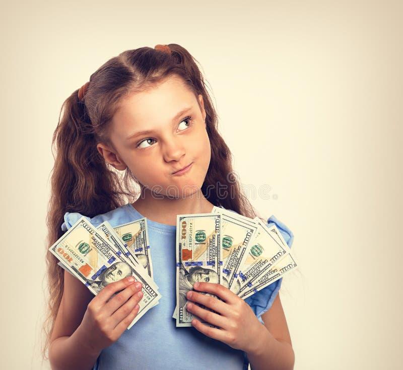 Lyckliga grimacing för ungeflicka för tvivel tänkande hållande pengar i hanen royaltyfri bild