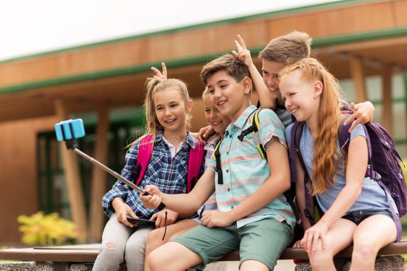 Lyckliga grundskolastudenter som tar selfie royaltyfri foto