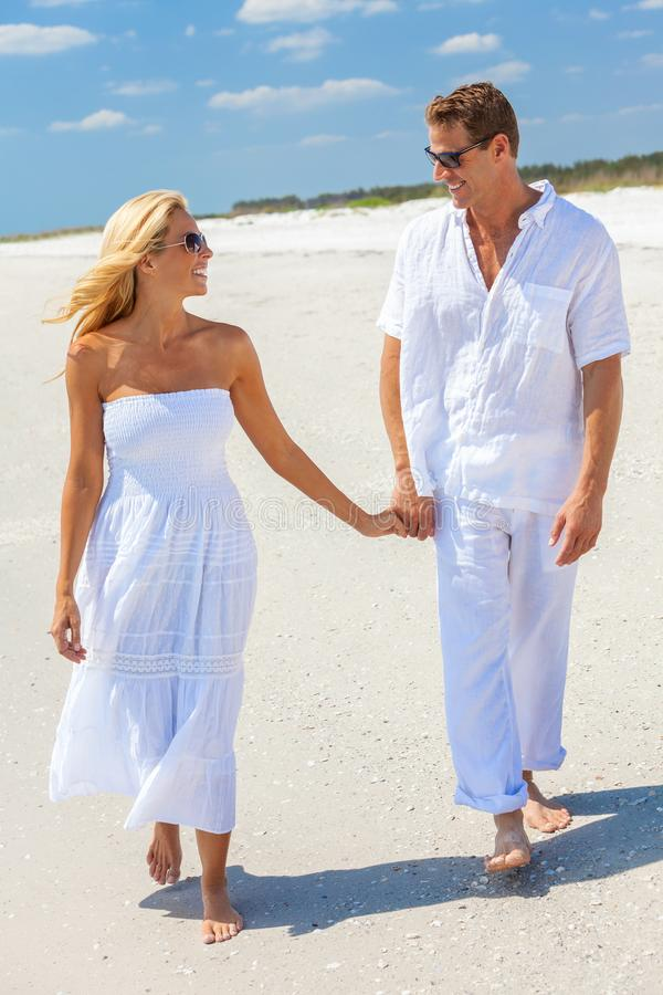 Lyckliga händer för innehav för mankvinnapar som går på en strand royaltyfri bild