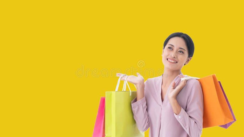 Lyckliga härliga asiatiska kvinnor ler hand som två rymmer shoppingpåsar arkivfoto