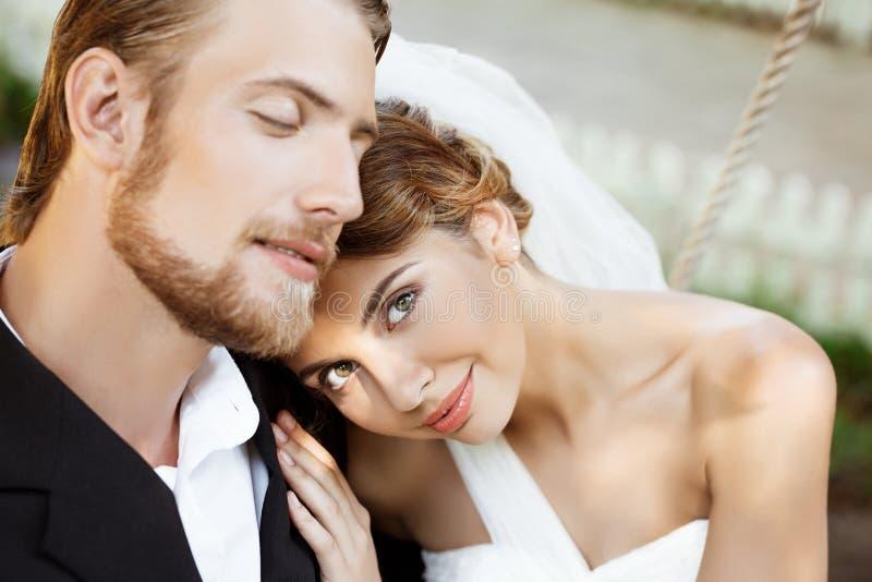 Lyckliga härliga nygifta personer i dräkt och bröllopsklänning som ler som tycker om royaltyfri foto