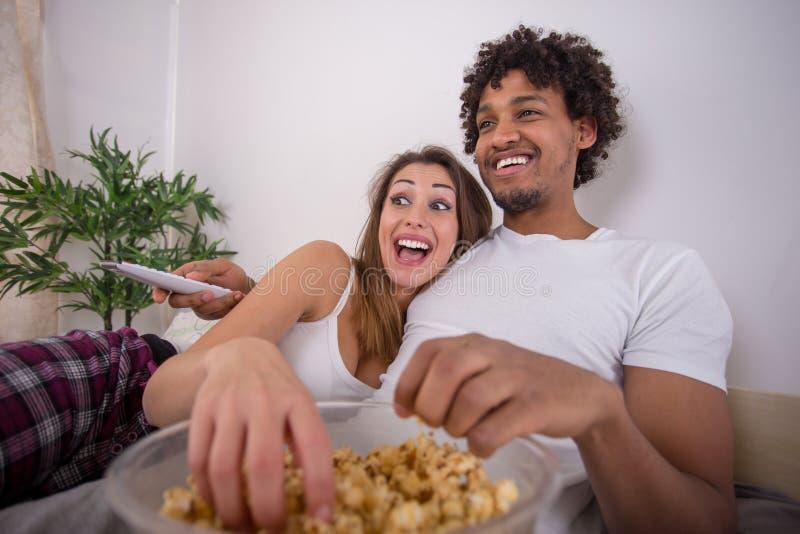 Lyckliga härliga par som äter popcorn, medan hålla ögonen på TV i säng arkivfoton