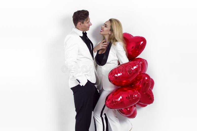 Lyckliga härliga par som poserar på vit bakgrund och rymmer ballonghjärta valentin för dag s royaltyfri bild