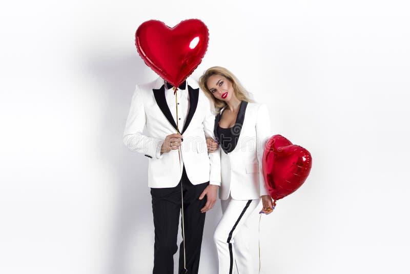 Lyckliga härliga par som poserar på vit bakgrund och rymmer ballonghjärta valentin för dag s royaltyfri fotografi