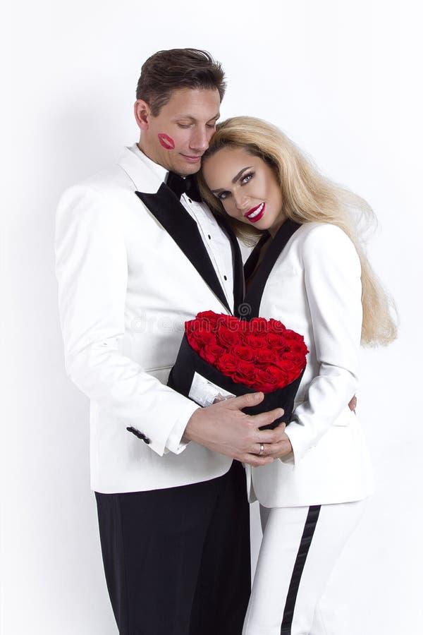 Lyckliga härliga par som poserar på vit bakgrund och rymmer blommaasken med röd hjärta Dag för valentin` som s gifta sig arkivfoton