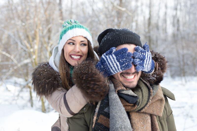 Lyckliga härliga par som spelar i snön fotografering för bildbyråer