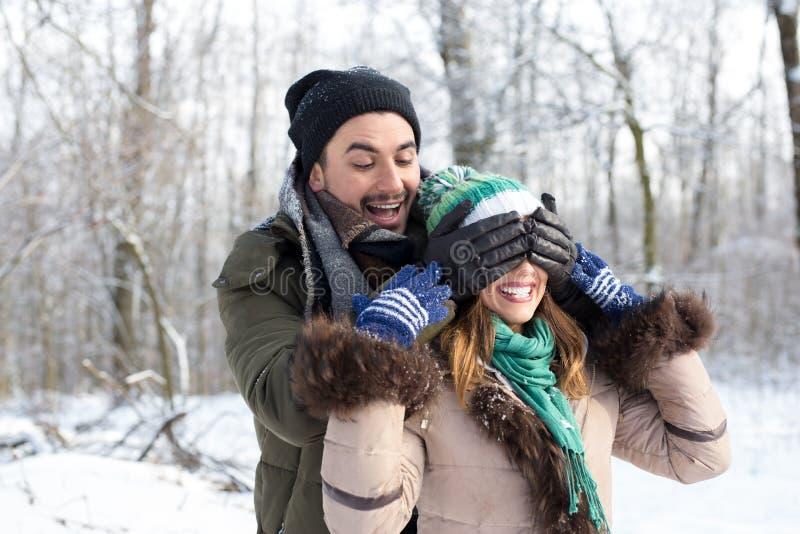 Lyckliga härliga par som spelar i snön royaltyfri foto