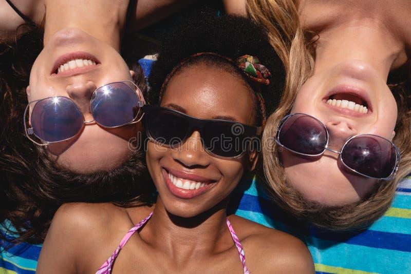 Lyckliga härliga unga kvinnor med solglasögon som ligger på stranden i solskenet arkivfoton