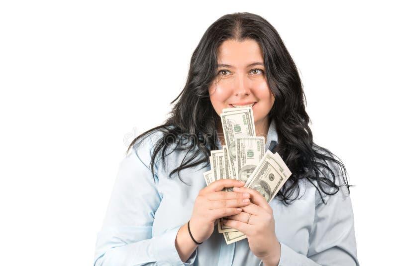 Lyckliga hållande amerikanska dollarpengar för ung kvinna i händer och munnen som isoleras på vit Positivt sinnesrörelsebegrepp royaltyfri foto