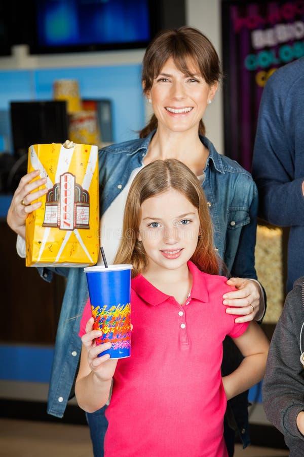 Lyckliga hållande mellanmål för moder och för dotter på bion royaltyfri fotografi