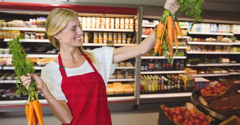 Lyckliga hållande morötter för små och medelstora företagkvinna royaltyfri bild
