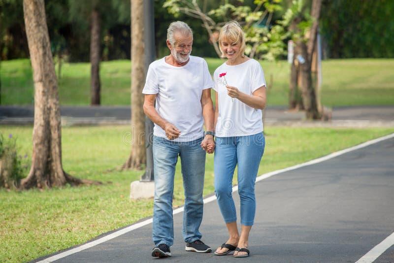 Lyckliga höga älska par som kopplar av på, parkerar att gå med blomman tillsammans i morgontid gamla människor som rymmer handen  royaltyfria bilder