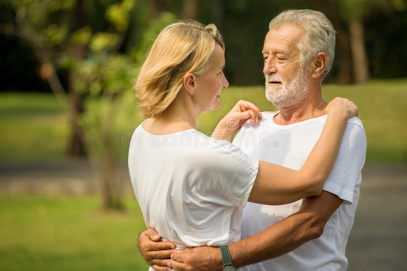 Lyckliga höga älska par som kopplar av på, parkerar att omfamna tillsammans i morgontid gamla människor som kramar och tycker om  royaltyfri fotografi