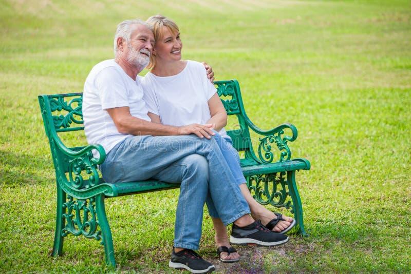Lyckliga höga älska par som kopplar av på, parkerar att omfamna tillsammans i morgontid gamla människor som sitter på en bänk i h royaltyfri fotografi