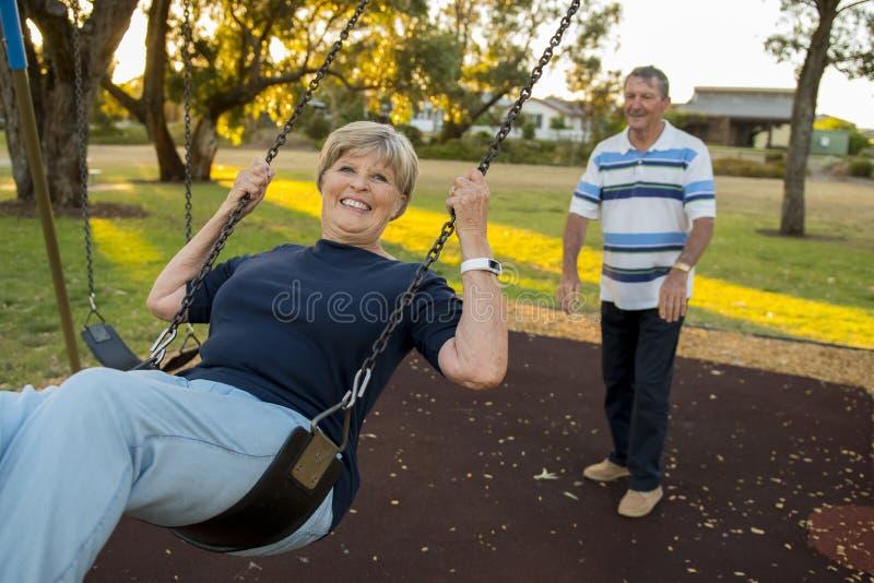Lyckliga höga amerikanska par omkring 70 år gammalt tycka om på gunga parkerar med den driftiga frun för maken som ler och har gy royaltyfria foton