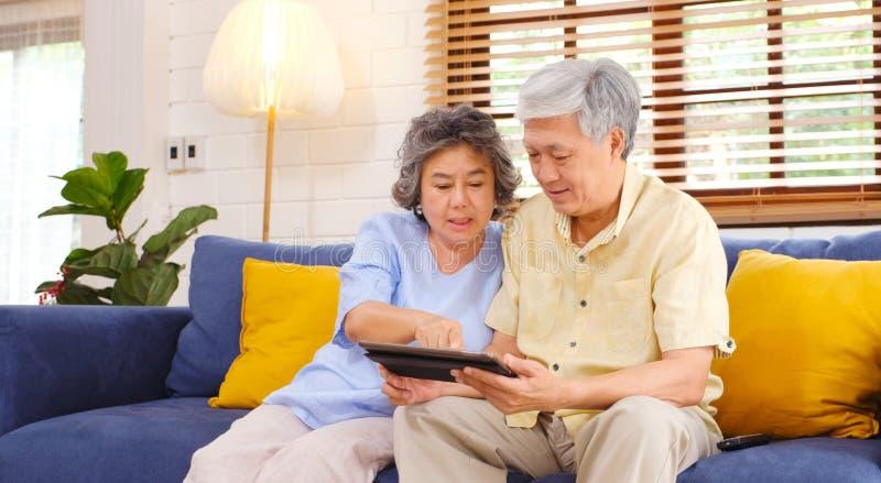 Lyckliga höga asiatiska par genom att använda den digitala minnestavladatoren som sitter på hemmastadd vardagsrumbakgrund för sof royaltyfri fotografi