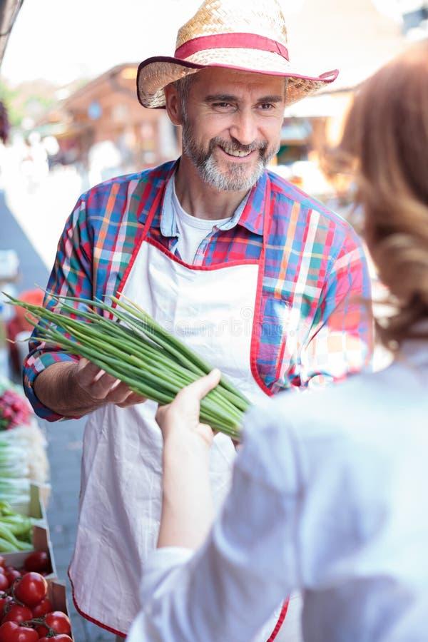 Lyckliga höga grönsaker för sälja för bonde organiska i en bondes marknadsplats royaltyfri foto