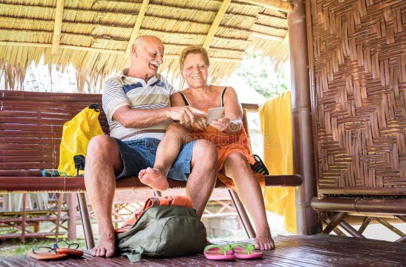 Lyckliga höga par genom att använda den mobila smarta telefonen på bungalowlyxsemesterorten - aktiv åldring och loppbegrepp allti royaltyfria foton