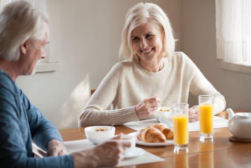 Lyckliga höga par har den sunda frukosten hemma royaltyfri bild