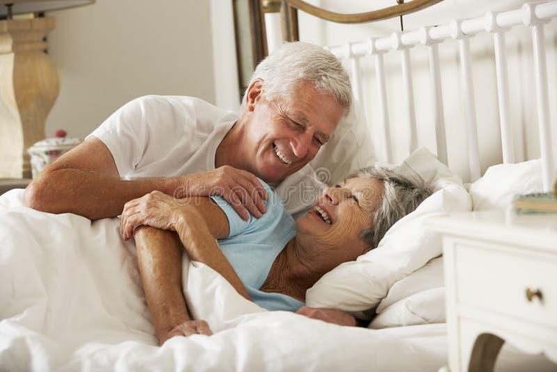 Lyckliga höga par i säng tillsammans arkivfoton
