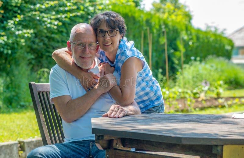 Lyckliga höga par i trädgården royaltyfri fotografi
