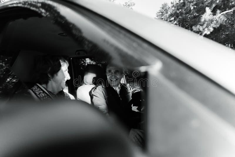 Lyckliga höga par inom den nya bilen arkivbild
