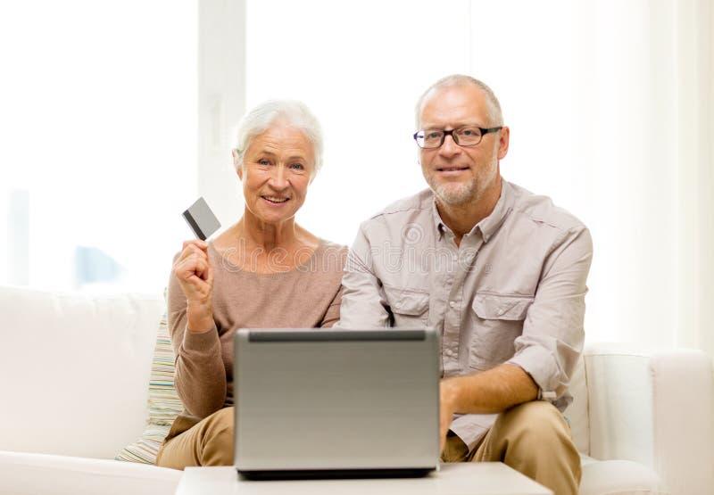 Lyckliga höga par med bärbara datorn och kreditkorten royaltyfri bild