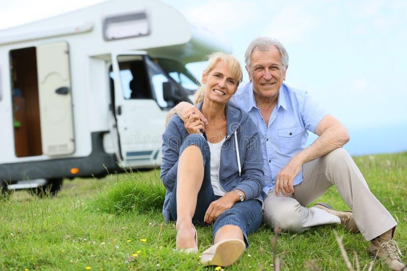 Lyckliga höga par med campa bilsammanträde i gräs royaltyfri fotografi