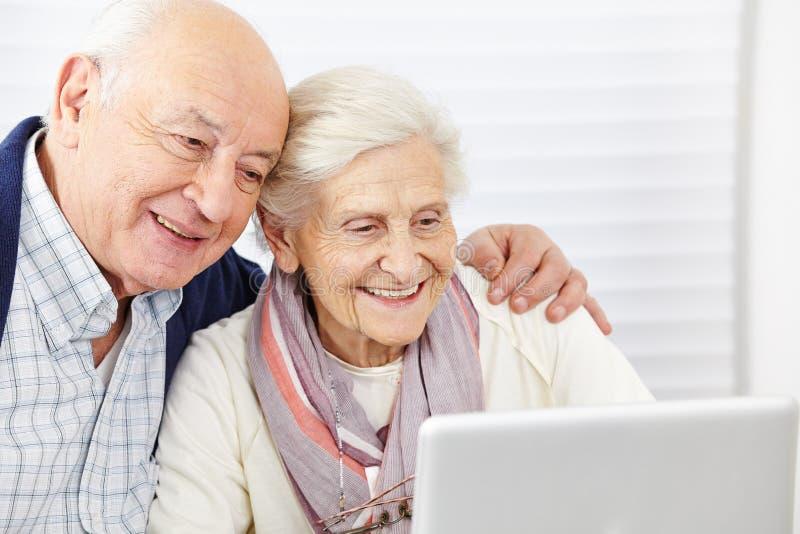 Lyckliga höga par med datoren arkivbild