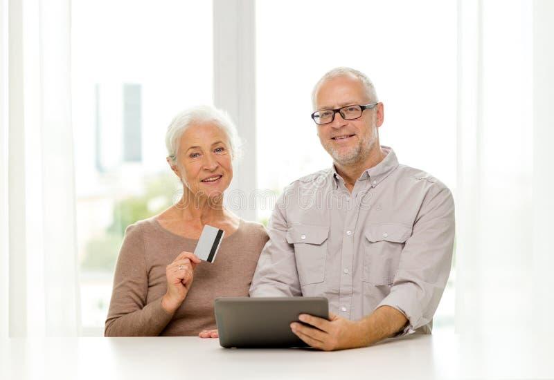 Lyckliga höga par med den minnestavlaPC och kreditkorten arkivbild