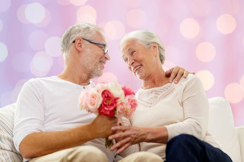 Lyckliga höga par med gruppen av blommor fotografering för bildbyråer