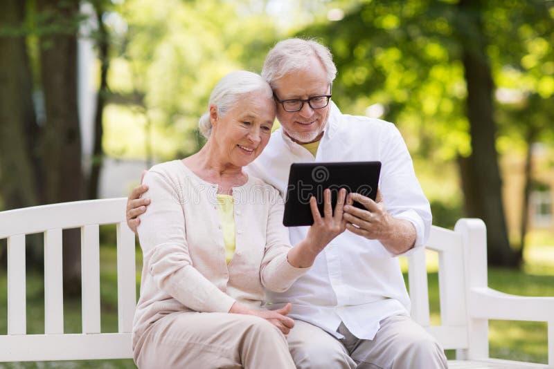Lyckliga höga par med minnestavlaPC på sommar parkerar arkivfoto