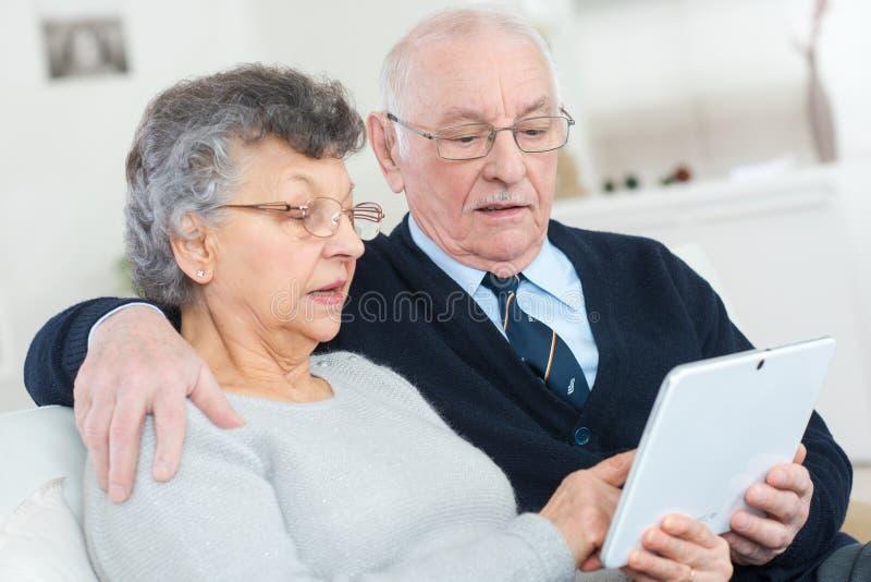 Lyckliga höga par med minnestavlaPCdatoren hemma arkivfoto