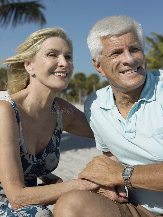 Lyckliga höga par på den tropiska stranden royaltyfria foton