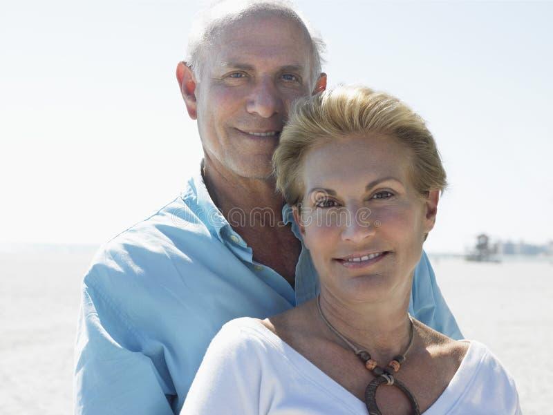 Lyckliga höga par på stranden royaltyfri bild