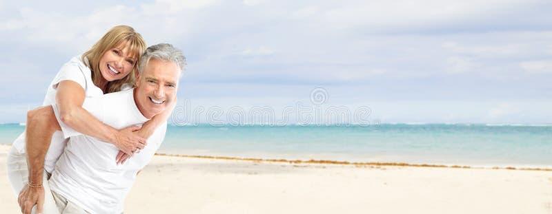 Lyckliga höga par på stranden. fotografering för bildbyråer