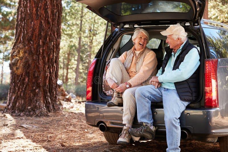 Lyckliga höga par sitter i den öppna bilstammen som förbereder sig för vandring arkivbild