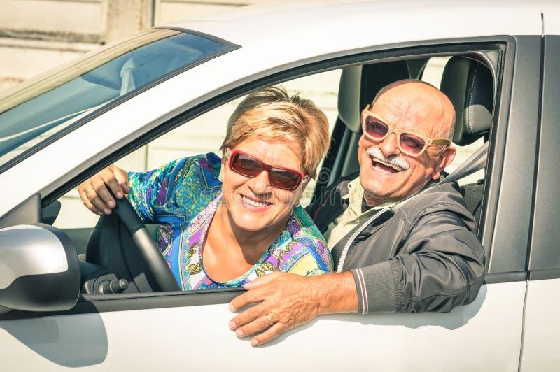 Lyckliga höga par som är klara för en bil, snubblar arkivfoton