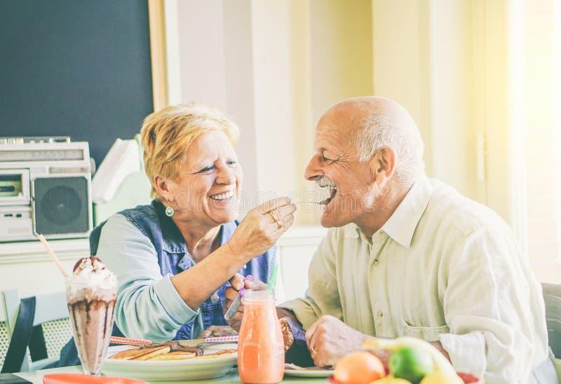Lyckliga höga par som äter pannkakor på frukosten i en stångrestaurang - gamla människor som har gyckel som tycker om mål på lunc fotografering för bildbyråer
