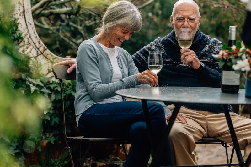 Lyckliga höga par som dricker vin som sitter på en tabell i deras trädgård Gammal kvinna som sitter med hennes make som dricker v royaltyfri bild