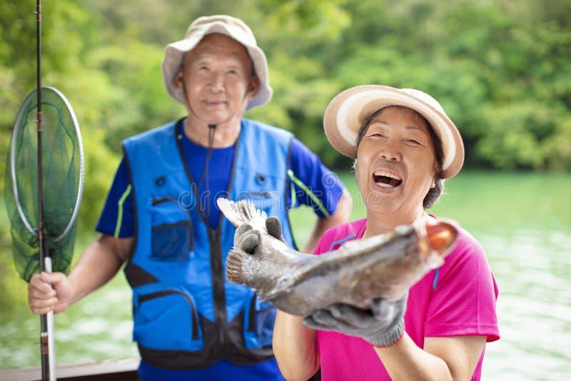 Lyckliga höga par som fiskar på lakesiden royaltyfri bild