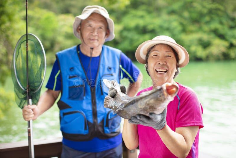 Lyckliga höga par som fiskar på lakesiden arkivfoton