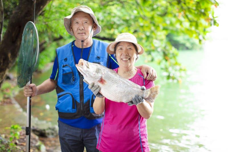Lyckliga höga par som fiskar på lakesiden royaltyfria bilder