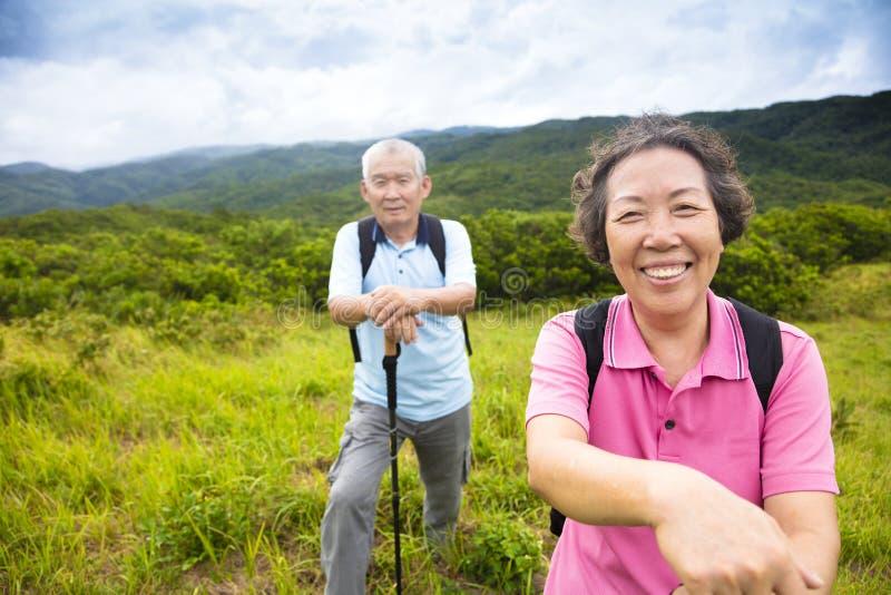 Lyckliga höga par som fotvandrar på berget royaltyfri bild